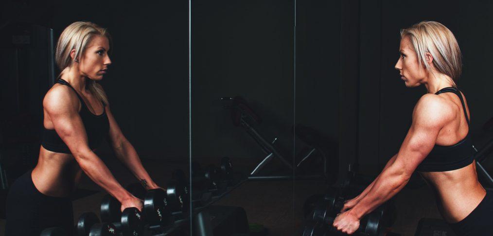 Mujer apoyada frente a unas pesas mirándose al espejo.